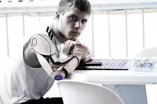 Individual sitting at a desk with robotic arms