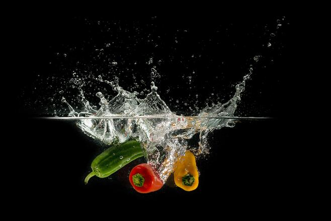 Peppers being dropped into water