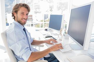 Smiling designer working at his desk in modern office.jpeg