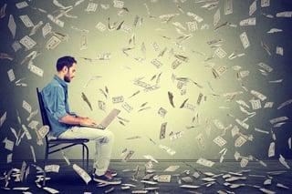 Young man using a laptop building online business making dollar bills cash falling down. Beginner IT entrepreneur under money rain. Success economy concept .jpeg